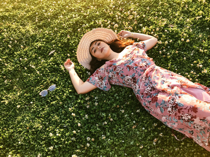 Girl in pink flowery dress and straw hat lying back on the grass on a bright day - Smartphone fashion photography shoot