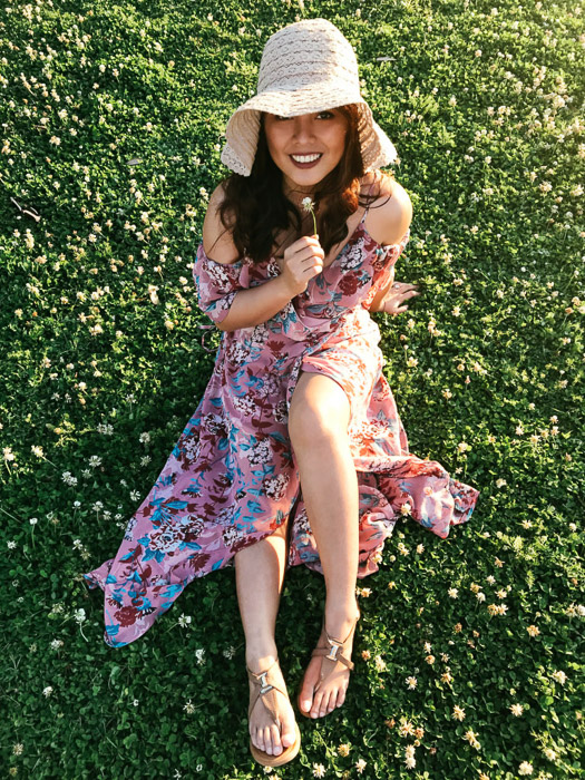 Girl in pink flowery dress and straw hat sitting on the grass and holding a white flower under her chin on a bright day - Smartphone fashion photography shoot