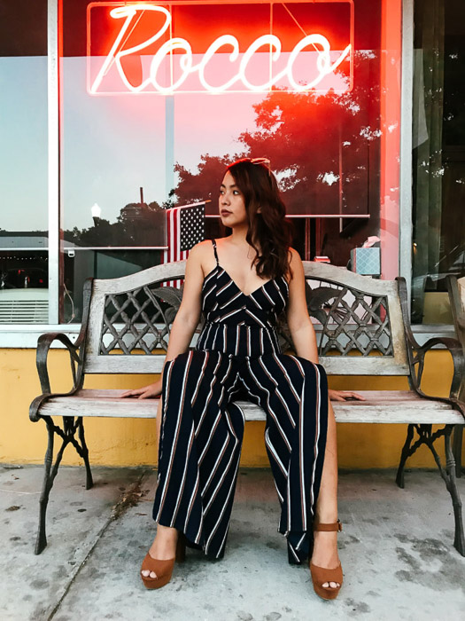 Portrait of a girl in a black and white striped outfit sitting on a wooden bench outside a cafe - Smartphone fashion photography shoot