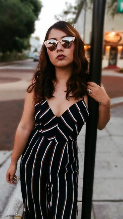 Portrait of a girl in a black and white striped outfit standing next to a pole in an urban street setting - Smartphone fashion photography shoot