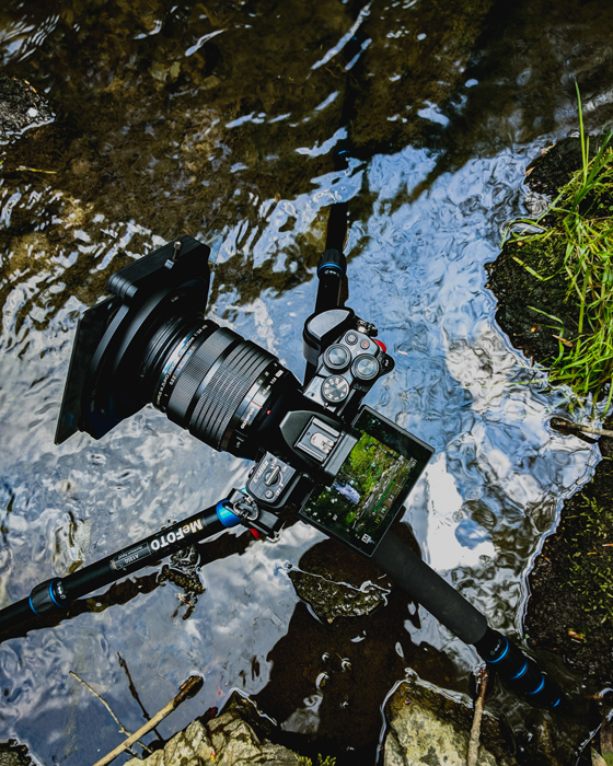 Overhead image of a tripod in a water stream set up to photograph waterfalls