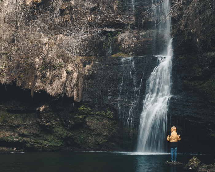 Photo of a person in yellow standing in front of a waterfall.