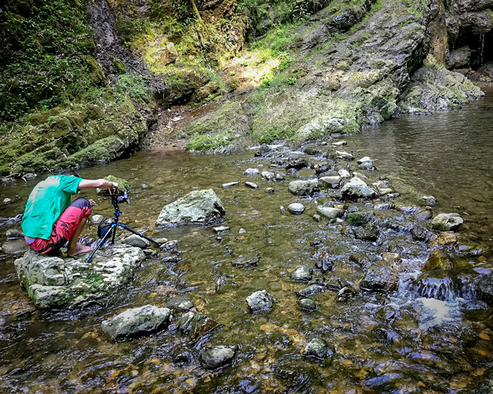 A photographer sitting on a rock with tripod and camera to take waterfall images