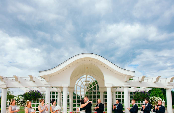 A bride and groom hugging between 4 bridesmaids and 5 bridegrooms, under a cloudy blue sky.
