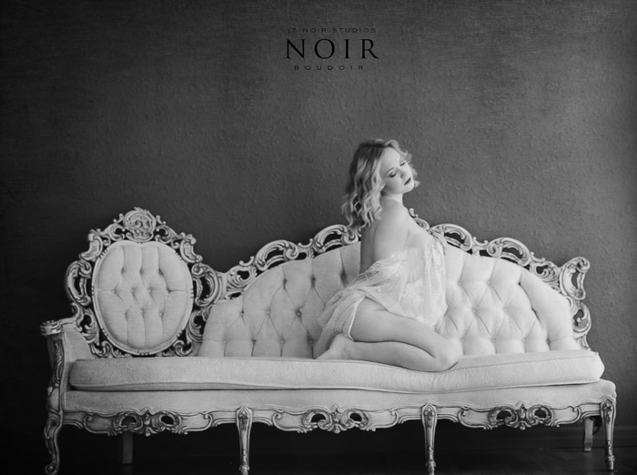 Black and white photo of a girl kneeling on a white chaise longue