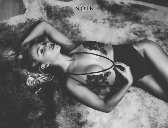Black and white boudoir photo of a blonde girl in black and white lingerie lying on her back