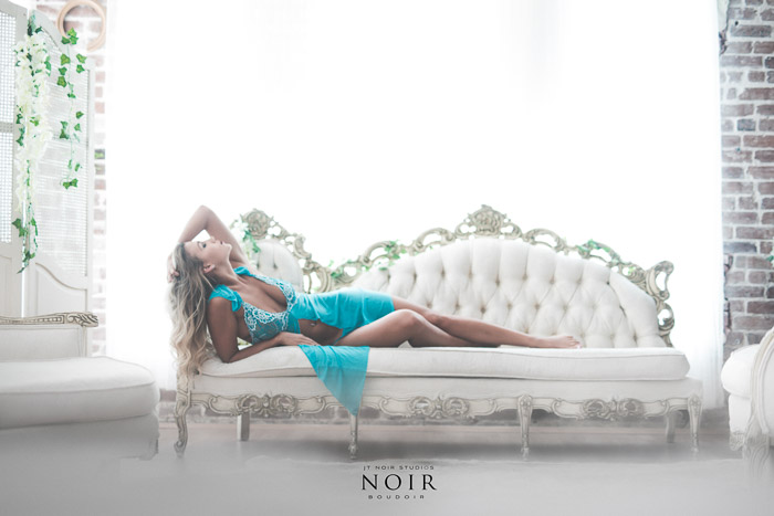 Light and airy boudoir shoot of a blonde girl in turquoise dress lying back on a white chaise lounge