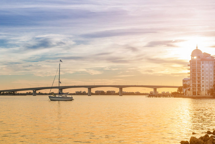 Dreamy photo of a bridge beside a small boat and buildings, soft shadows and colour achieved by shooting during 'Golden Hour'. Landscape photography