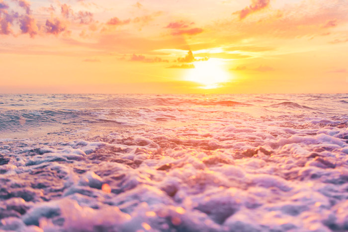 Intensely coloured sunset over rushing pink waves. landscape photography.