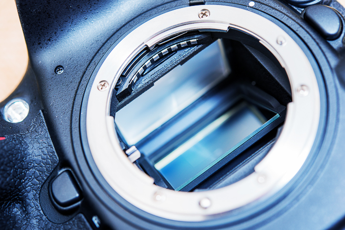 A close up of a camera body without lens. Blue hour photography