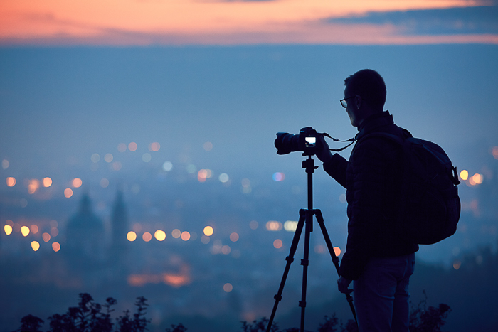 A photographer sets up his camera on a tripod for blue hour photography