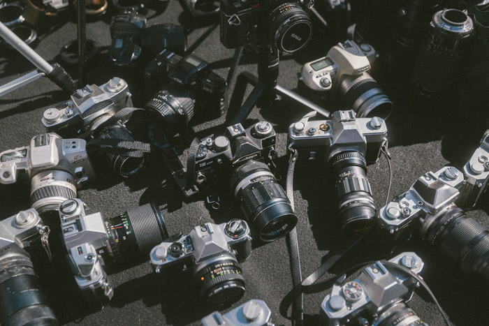 Overhead photo of a collection of different used cameras. Buying used lenses and used cameras.