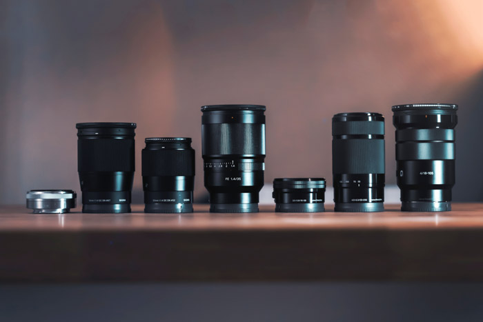Photo of a collection of different lenses on a wooden table. Buying used lenses and used cameras.
