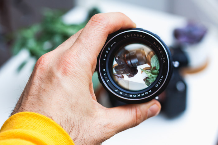 Photo of a hand holding a Minolta lens framing a DSLR camera. Buying used lenses and used cameras.