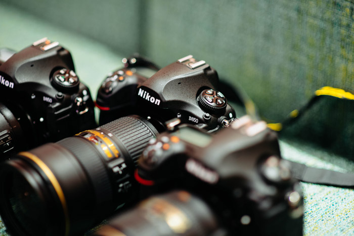 Photo of a Nikon DSLR on green background. Buying used lenses and used cameras.