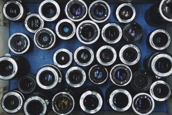 Overhead photo of a collection of different lenses on blue background. Buying used lenses and used cameras.