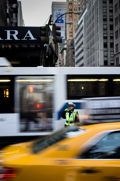 A street scene showing blurry traffic with a traffic warden between the moving cars. depth of field photography.