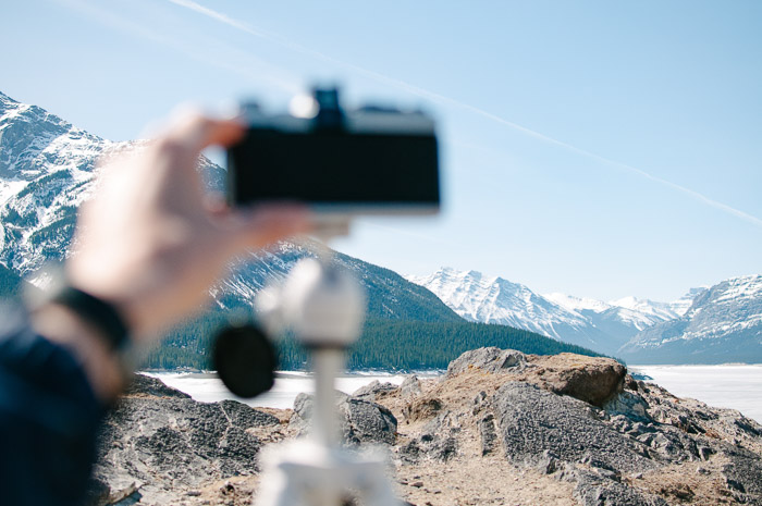 A hand holding a camera in front a mountainous landscape - using depth of field to blur the foreground
