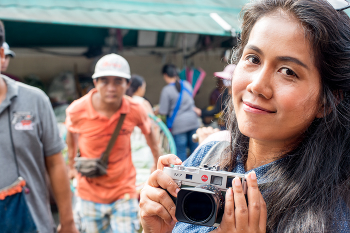 A girl holding a camera in Chiang Mai, Thailand, documentary photography