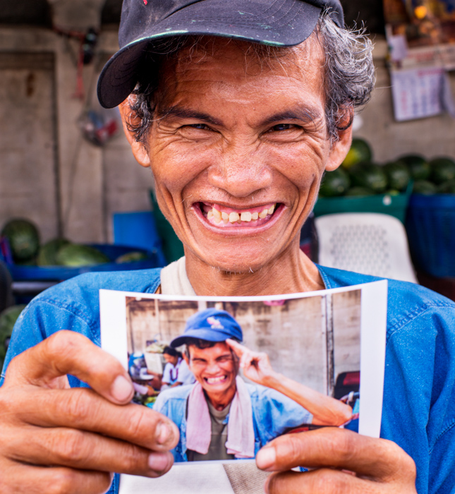 A market porter holding a picture of himself in Chiang Mai, Thailand, documentary photography