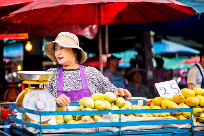Documentary photography of a woman standing behind a basket of fruit at a busy market in Chiang Mai, Thailand