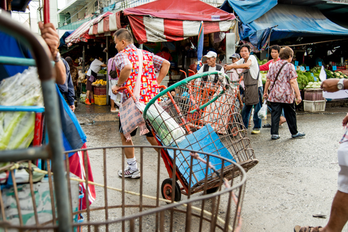 Documentary photography portrait of a man pulling steel carts at Muang Mai Market, Chiang Mai, Thailand.