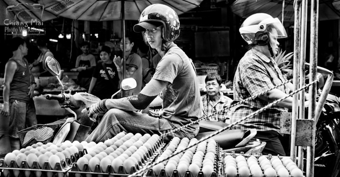 Black and white documentary photography of men on motorbikes riding through a busy market in Chiang Mai, Thailand