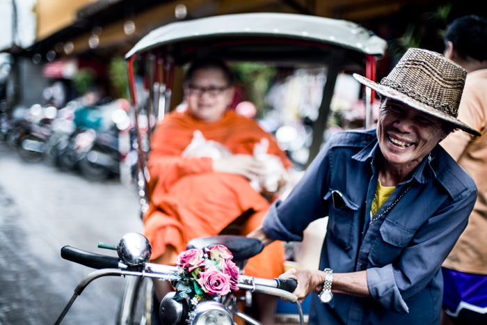 Documentary photography portrait of a saamlor rider and a monk in a Market in Chiang Mai, Thailand.