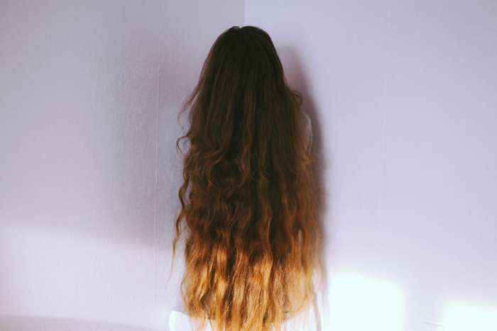 A girl with her long brown hair covering her face standing in a pink room posed for a faceless portrait.