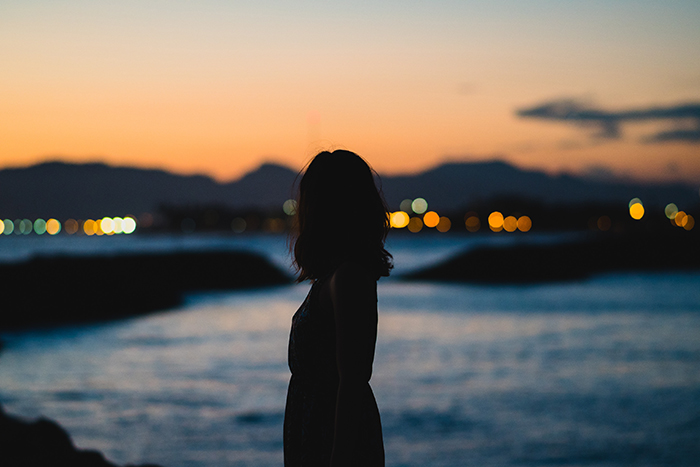 A silhouette of a woman standing in the foreground of an evening seascape - faceless portrait photography