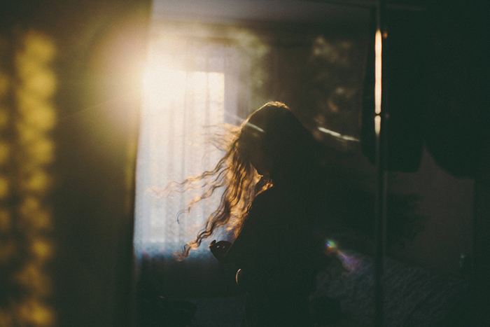 Dreamy low light silhouette of a woman standing - faceless portrait photography
