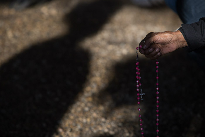 a hand holding rosary beads against a shadowing background. Photo by Amber Bracken. Famous photographers to follow online