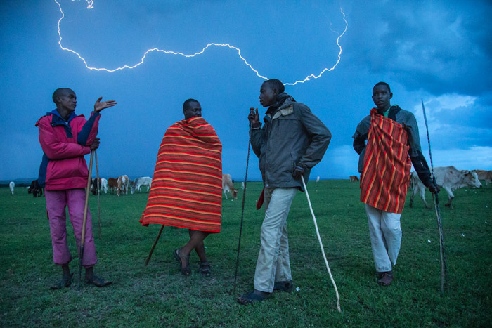 Night photography of 4 African men standing outdoors with lightning striking in the background. Charlie Hamilton James. Famous photographers to follow.