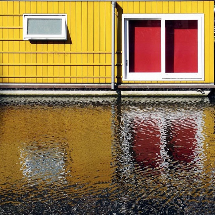 Photo of a yellow house with red windows reflected in the water below by Website | Facebook | Instagram Dirk Bakker. Famous photographers to follow.