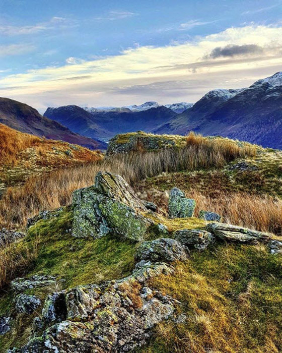 Magnificent grassy landscape with mountainous background, landscape photography by Jane Samuels. Famous photographers to follow.