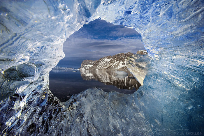 A seascape photographed through a hole in ice by Paul Nicklen. Famous photographers to follow.