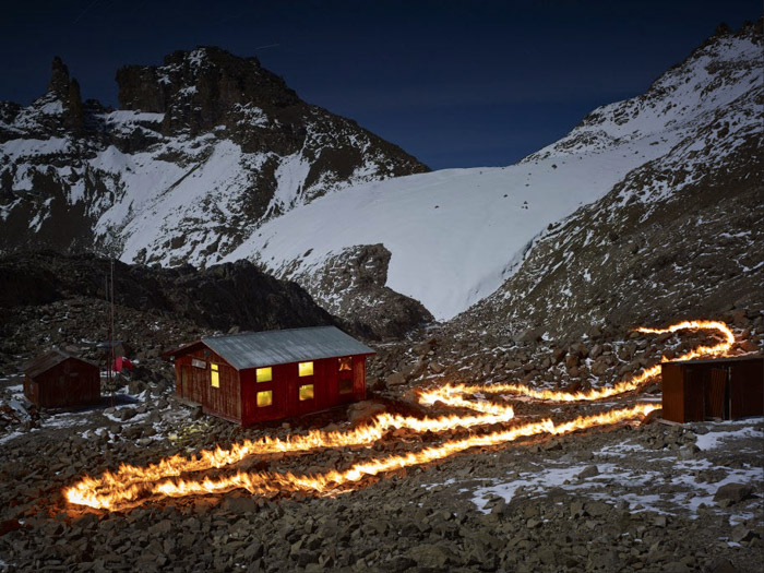 Photo of a firetrail by a woodenhouse in a snowy mountainous landscape by Simon Norfolk. famous photographers to follow.