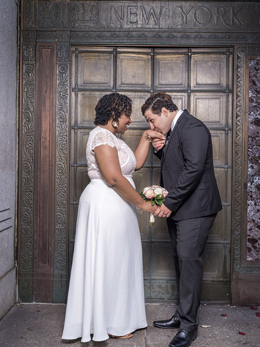 Wedding photography of newlywed couple holding hands outside a doorway by Wayne Lawrence. Famous photographers to follow.