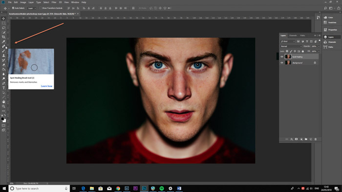 Screenshot of photoshop interface using the spot healing tool for smooth skin photoshop tutorial.