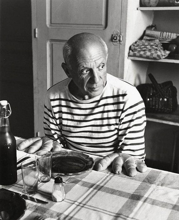 Robert Doisneau black and white photograph of Pablo Picasso sitting at a table posed as if bread were his hands