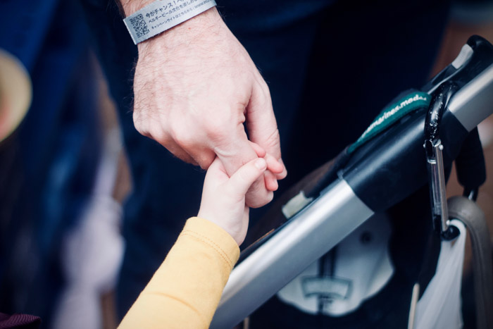 Close up photograph of an adults hand holding a small childs hand as an example of big vs small juxtaposition examples