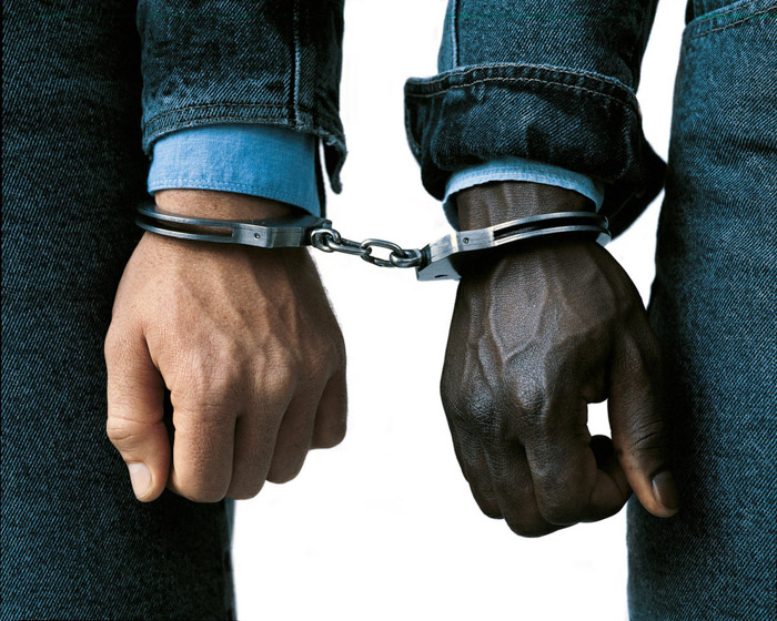Oliviero Toscani close up of two mens hands handcuffed together - one black and one white as a symbol of juxtaposed stereotypes