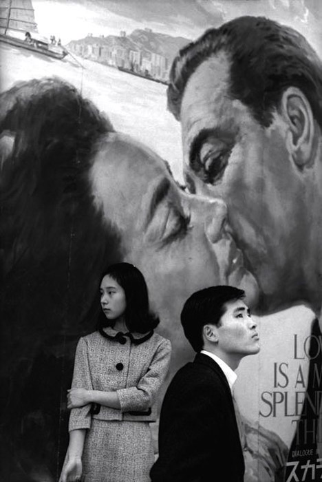 Henri Cartier-Bresson photo of a man and woman standing juxtaposed against a painted background of a couple kissing.