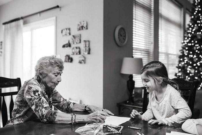 Black and white photograph of a grandmother and child at a table colouring in a book