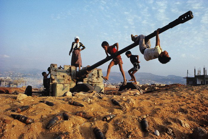 Documentary photography of children playing around a disused and abandoned artillery weapon.