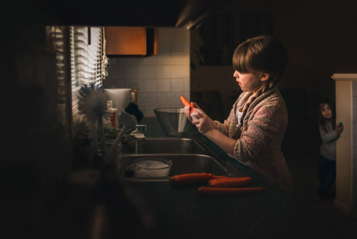 A photo of a little girl peeling carrots at the kitchen sink