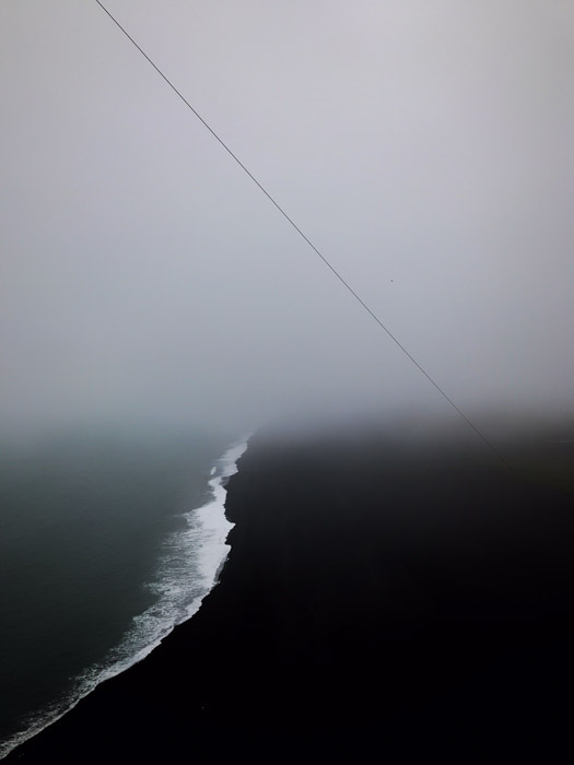 Atmospheric dark image of the coastline juxtaposed by overcast sky