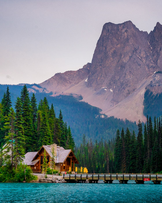 Photo of a wooden house by a bridge over blue water with a mountainous background. Landscape photography composition