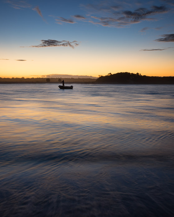 A figure in a small boat on water at evening. Landscape photography composition