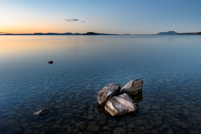A group of rocks in a still sea at sunset. Landscape photography composition